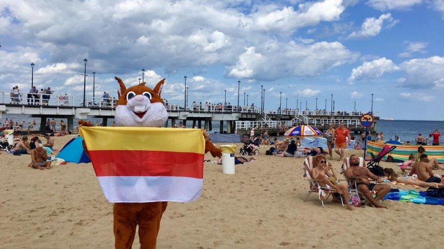 WiewiórINKA na plaży, trzymając flagę Inowrocławia.